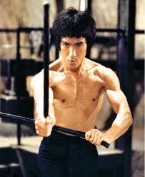 تصویری از بروس لی با دو چوب اسکریما در فیلم اژدها وارد می شود
